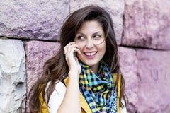 Porträt der schönen lächelnden Frau, die am Telefon im Freien spricht Lizenzfreie Stockbilder