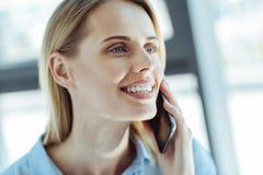 Porträt der schönen lächelnden Frau, die am Telefon spricht Lizenzfreie Stockfotografie