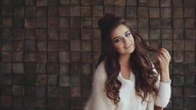 Porträt der schönen lächelnden Frau mit hellem bilden auf dem braunen Hintergrund stock video
