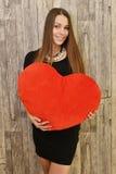 Porträt der schönen lächelnden Frau mit rotem Herzen Stockfotografie