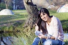 Porträt der schönen lachenden Frau, die ihr Geld im Park zählt Lizenzfreies Stockfoto