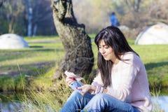 Porträt der schönen lachenden Frau, die ihr Geld im Park zählt Stockbild