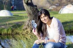 Porträt der schönen lachenden Frau, die ihr Geld im Park zählt Stockfoto
