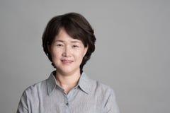 Porträt der schönen reifen Frau, die gegen grauen Hintergrund aufwirft Lizenzfreie Stockfotos