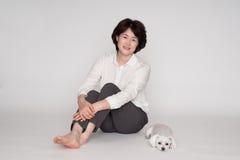 Porträt der schönen reifen Frau, die gegen grauen Hintergrund aufwirft Lizenzfreies Stockfoto