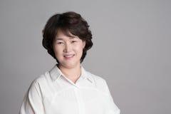 Porträt der schönen reifen Frau, die gegen grauen Hintergrund aufwirft Lizenzfreies Stockbild