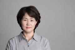 Porträt der schönen reifen Frau, die gegen grauen Hintergrund aufwirft Stockbilder