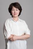 Porträt der schönen reifen Frau, die gegen grauen Hintergrund aufwirft Lizenzfreie Stockfotografie