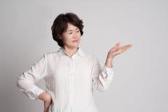 Porträt der schönen reifen Frau, die gegen grauen Hintergrund aufwirft Stockfotografie