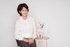 Porträt der schönen reifen Frau, die gegen grauen Hintergrund aufwirft Lizenzfreie Stockbilder