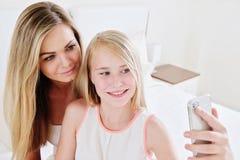 Porträt der schönen reifen Mutter und ihrer der Tochter, die ein selfie unter Verwendung des intelligenten Telefons und des Läche lizenzfreie stockbilder