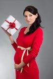 Porträt der schönen schwangeren Frau im roten Kleid mit Geschenkbox Stockfotos