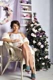 Porträt der schönen schwangeren jungen Frau nahe einem Weihnachtsbaum Lizenzfreies Stockfoto