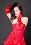 Porträt der schönen sexy Brunettefrau mit dem langen Haar im roten Satinkleid Stockfotos