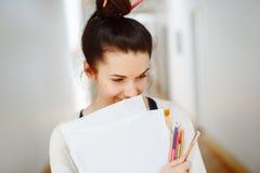 Porträt der schönen weißen kaukasischen jungen BrunetteStudentin, des weiblichen Zeichnungsdesignerkünstlers mit Papier und der B Lizenzfreie Stockfotos