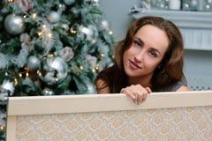 Porträt der Schönheit auf dem Sofa, das nahe dem Weihnachtsbaum sitzt stockfotografie