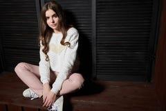 Porträt der Schönheit in den rosa Hosen und in der weißen Strickjacke Stockfotos