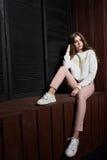 Porträt der Schönheit in den rosa Hosen und in der weißen Strickjacke Lizenzfreies Stockfoto