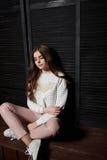 Porträt der Schönheit in den rosa Hosen und in der weißen Strickjacke Lizenzfreie Stockfotografie
