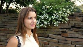 Porträt der Schönheit vor dem hintergrund einer Wand von den Steinen und von den Blumen Frau, die in den Stein geht stock video