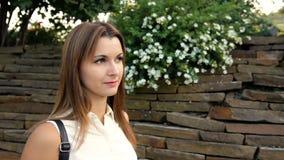 Porträt der Schönheit vor dem hintergrund einer Wand von den Steinen und von den Blumen Frau, die in den Stein geht stock video footage