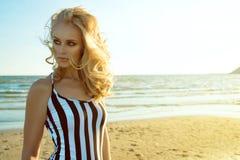 Porträt der schicken blonden Frau im gestreiften Kleid, das an der Küste steht und beiseite mit provozierenden grünen Augen schau Stockfoto