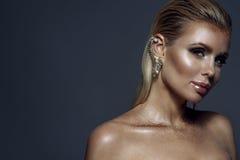 Porträt der schicken herrlichen blonden Frau mit dem nassen Haar, künstlerischem funkelndem Make-up und der Stulpe auf ihrem Ohr Stockfoto