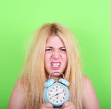 Porträt der schläfrigen jungen Frau im Chaos, das Uhr gegen g hält Lizenzfreie Stockfotos