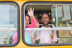 Porträt der Schule scherzt wellenartig bewegende Hand vom Bus Lizenzfreie Stockfotos