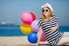Porträt der schwangeren Frau mit Sonnenbrille und Hut Stockbilder