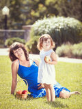 Porträt der schwangeren Mutter und der Tochter, die draußen spielen umarmt Lizenzfreie Stockfotos