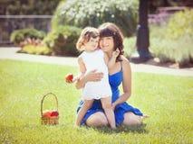 Porträt der schwangeren Mutter und der Tochter, die draußen spielen umarmt Stockbild
