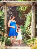 Porträt der schwangeren Mutter und der Tochter, die draußen spielen umarmt Stockbilder