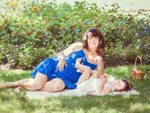 Porträt der schwangeren Mutter und der Tochter, die draußen spielen umarmt Stockfotos