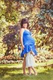Porträt der schwangeren Mutter und der Tochter, die draußen spielen umarmt Stockfotografie