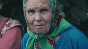 Porträt der sehr alten Frau allein in einem Schal am Garten im Freien stock video