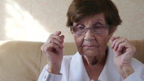 Porträt der sehr alten Frau setzte an und entfernt Gläser stock video footage
