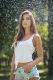 Porträt der sexy Frau im Spray des Wassers mit weißem T-Shirt Sie hat eine gute leichte Haut, sinnliche Lage, und sie lächelt stockfotos
