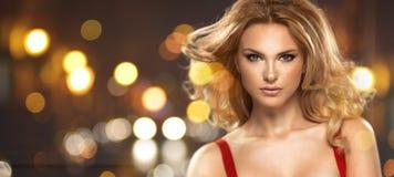 Porträt der sexy Frau mit dem langen gelockten Haar Stockfotografie