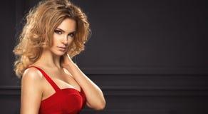 Porträt der sexy Frau mit dem langen gelockten Haar Lizenzfreie Stockbilder