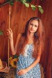 Porträt der sexy jungen Frau, die auf dem Heu sitzt Stockfotos