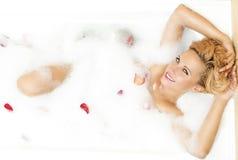 Porträt der sexy sinnlichen kaukasischen blonden Frau in der schäumenden Badewanne gefüllt mit Rose Petals Lizenzfreie Stockfotos