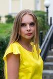 Porträt der sinnlichen modernen jungen Frau im gelben Kleid im Freien Stockbild