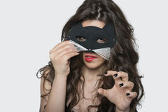 Porträt der sinnlichen tragenden Katzenmaske der jungen Frau beim Beißen der Lippe über grauem Hintergrund Stockbilder
