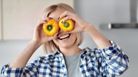 Porträt der spielerischen jungen Frau, die Augen durch mittlere Nahaufnahme des gelben Pfeffers bedeckend lächelt stock video footage