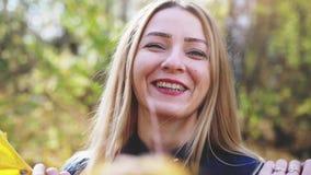 Portr?t der spielerischen reizenden jungen Frau mit gelbem Blatt im Herbstwald 3840x2160 Langsame Bewegung stock footage