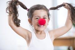 Porträt der spielerischen tragenden Clownnase des kleinen Mädchens, die zu Hause Zöpfe hält Stockfoto