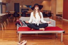 Porträt der sportlichen jungen weißen kaukasischen Geschäftsfrau des dünnen Sitzes, die meditiert, Yoga tuend, trainiert stockbild