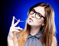 Porträt der strengen jungen Frau mit Sonderlingsgläsern und Kaugummi Lizenzfreies Stockfoto
