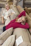 Porträt der Tochter entspannend auf Sofa während Mutter, die im Möbelgeschäft schaut stockfotos